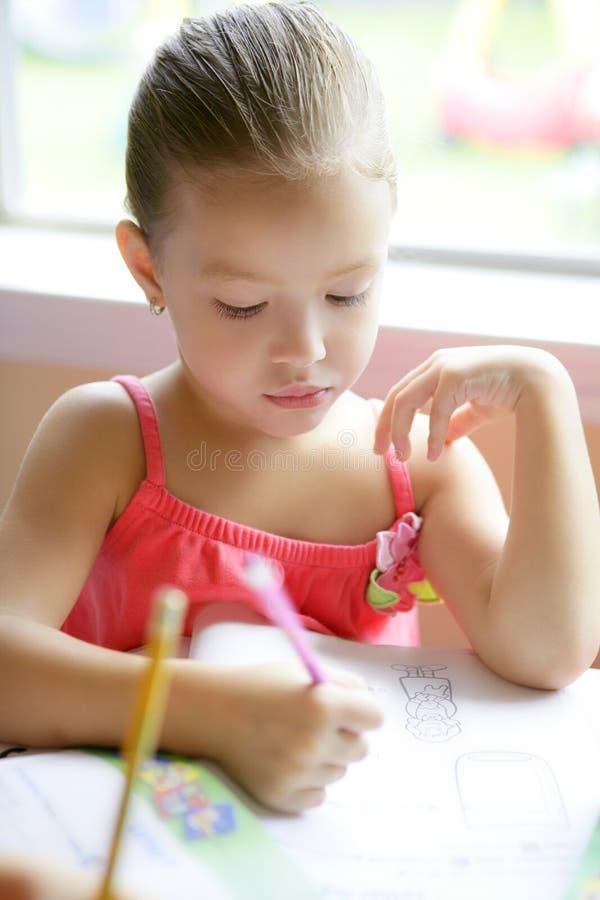 Escrita pequena da menina da criança na mesa da escola fotografia de stock