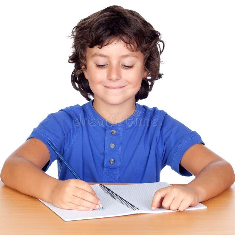 Escrita pequena de sorriso do estudante no caderno foto de stock royalty free