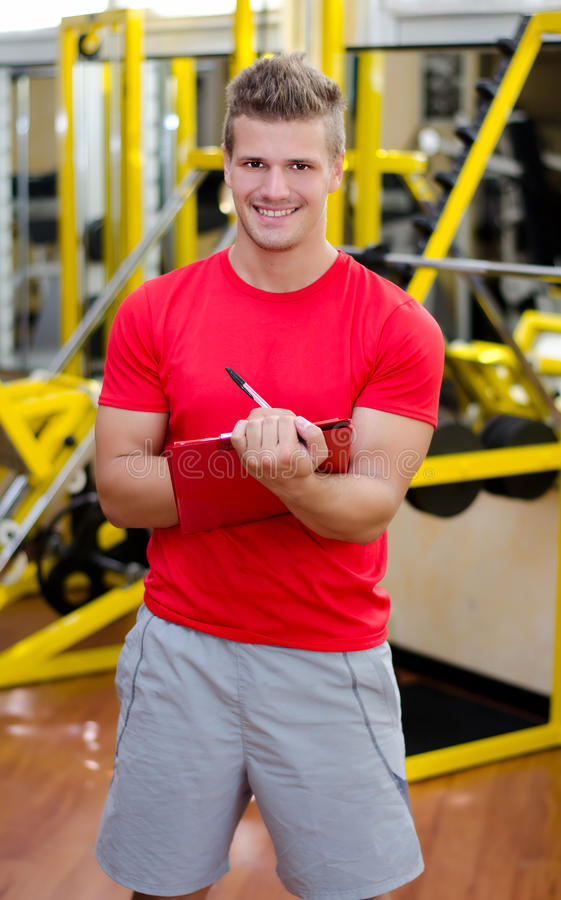 Escrita pessoal masculina nova do instrutor no sorriso da prancheta fotos de stock royalty free