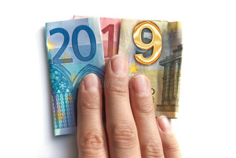 2019 escrito con los billetes de banco de los euros en una mano aislada en blanco imagen de archivo