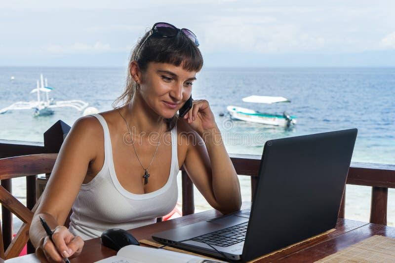 Escritor bonito joven del freelancer de la mujer que trabaja con la libreta del ordenador portátil y el teléfono delante del mar  fotos de archivo libres de regalías