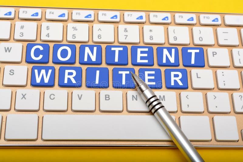 Escritor contento en llaves del ordenador portátil con el primer de la pluma foto de archivo