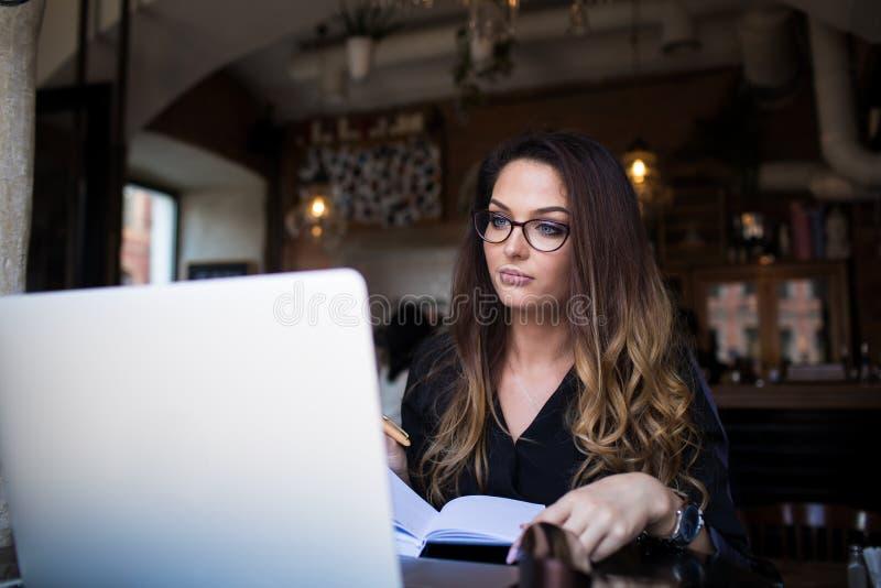 Escritor de comercialización profesional de sexo femenino que prepara un artículo para la publicación usando netbook fotografía de archivo