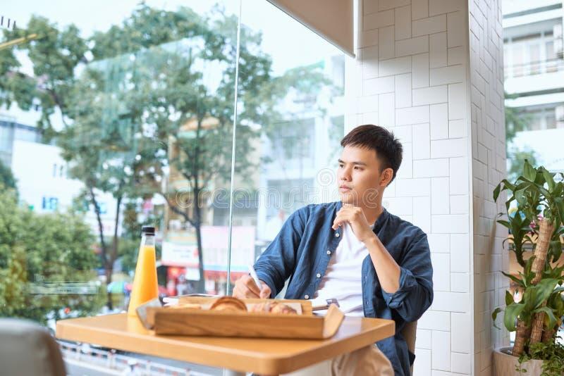 Escritor de sexo masculino hermoso del freelancer que crea el artículo de la publicidad para imagen de archivo libre de regalías