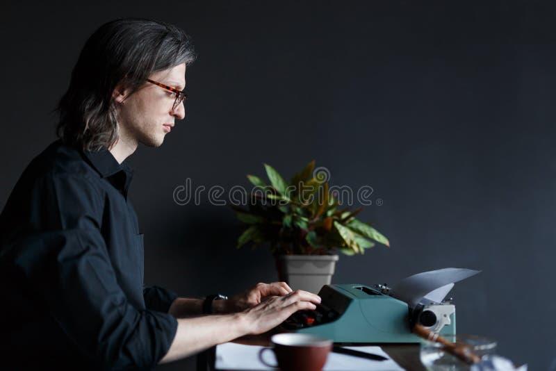 Escritor del hombre joven en camisa negra con el pelo largo, en vidrios mecanografiando en una máquina de escribir vieja en una t imagen de archivo libre de regalías
