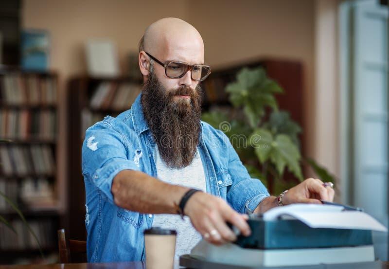 Escritor elegante barbudo que mecanografía en la máquina de escribir fotos de archivo libres de regalías