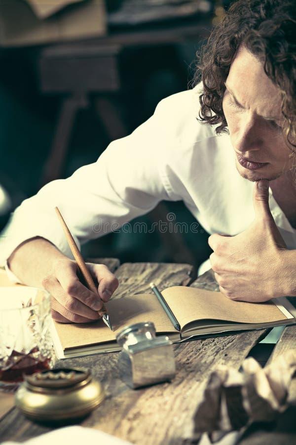 Escritor en el trabajo Escritor joven hermoso que se sienta en la tabla y que escribe algo en su bloc de bocetos imágenes de archivo libres de regalías