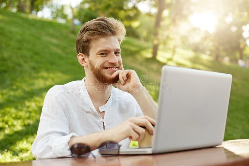 Escritor europeo del pelirrojo hermoso con el peinado elegante y barba, sentándose en parque soleado, mirando la cámara, trabajan fotos de archivo libres de regalías