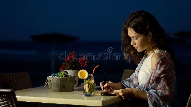 Escritor fêmea inspirado que faz anotações no caderno, trabalhando na história de amor romântica imagem de stock