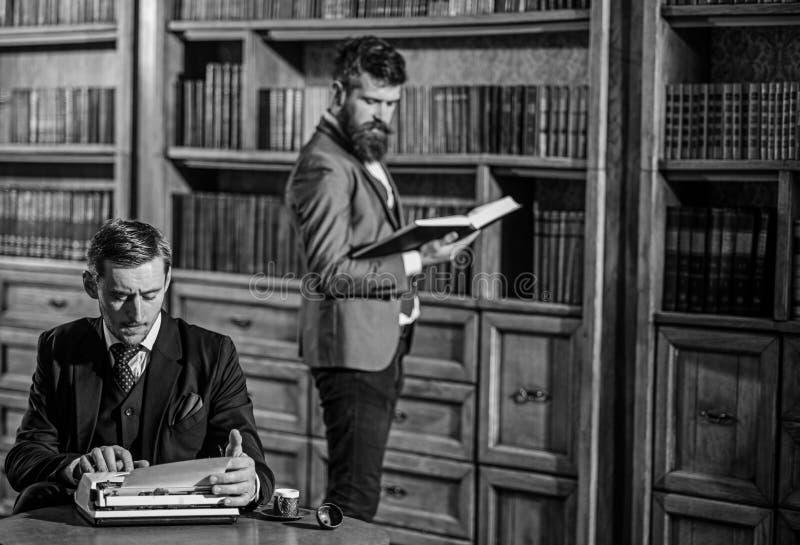 Escritor pasado de moda joven con la m?quina de escribir en biblioteca con el amigo barbudo foto de archivo libre de regalías