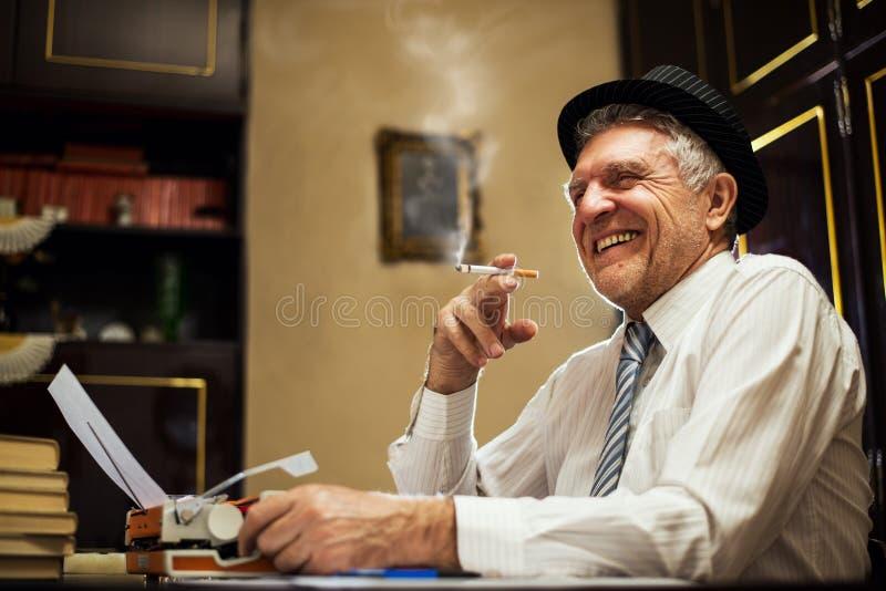 Escritor retro do homem superior com um cigarro foto de stock