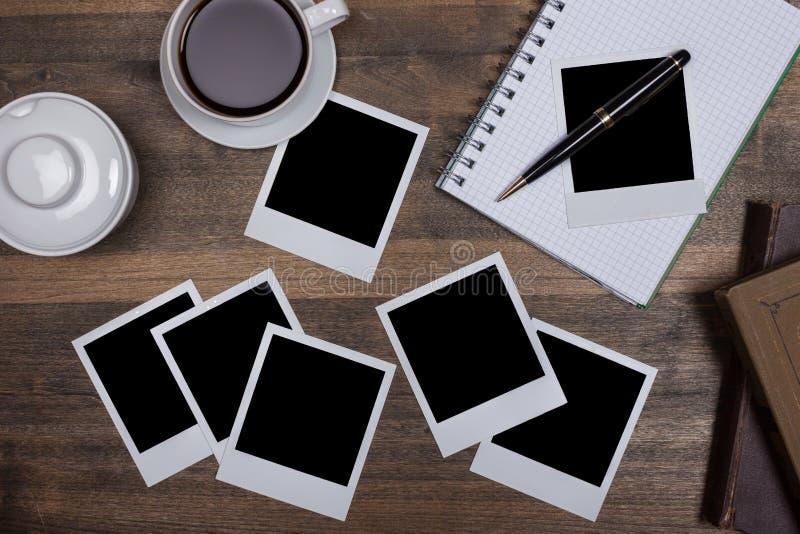 Escritorio con el cuaderno, el café y polaroides en blanco foto de archivo