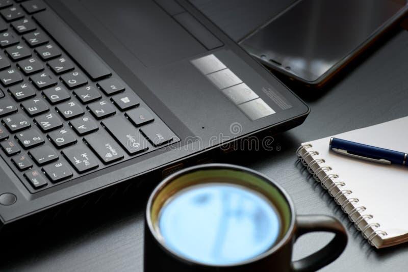 Escritorio con el ordenador portátil, el teléfono elegante, los cuadernos, las plumas, las lentes y una taza de té Opinión de áng foto de archivo