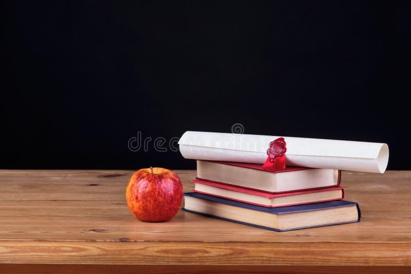 Escritorio de la escuela con el fondo del negro del diploma imagen de archivo libre de regalías