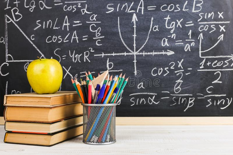 Escritorio de la escuela en sala de clase, con los libros en el fondo del tablero de tiza con f?rmulas escritas El d?a del profes imagenes de archivo