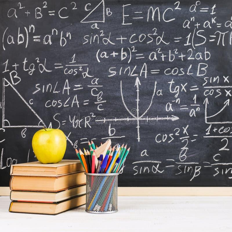Escritorio de la escuela en sala de clase, con los libros en el fondo del tablero de tiza con f?rmulas escritas El d?a del profes imagen de archivo