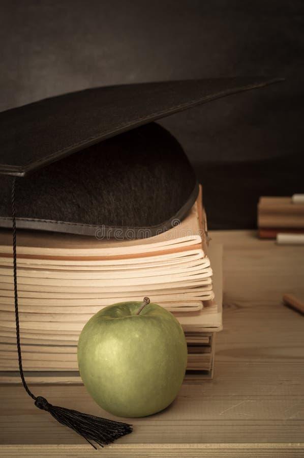 Escritorio de los profesores con los libros apilados, el birrete, Apple y Chalkb fotografía de archivo
