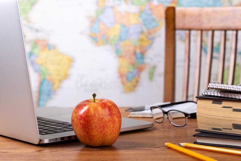 Escritorio de los profesores de escuela con el mapa del mundo en fondo imagen de archivo