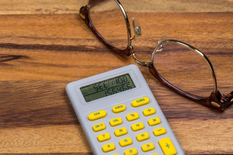 Escritorio de madera con los vidrios y la calculadora del ojo imagen de archivo libre de regalías