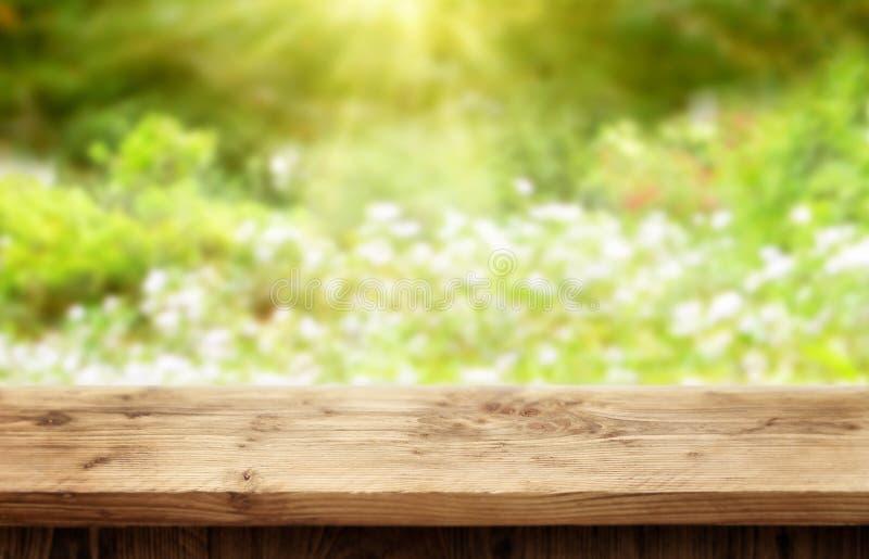 Escritorio de madera en el fondo del bokeh para la primavera o el verano imagenes de archivo