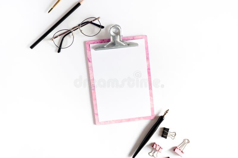 Escritorio de Ministerio del Interior con el tablero rosado, vidrios, clips de papel, brocha, lápiz fotos de archivo