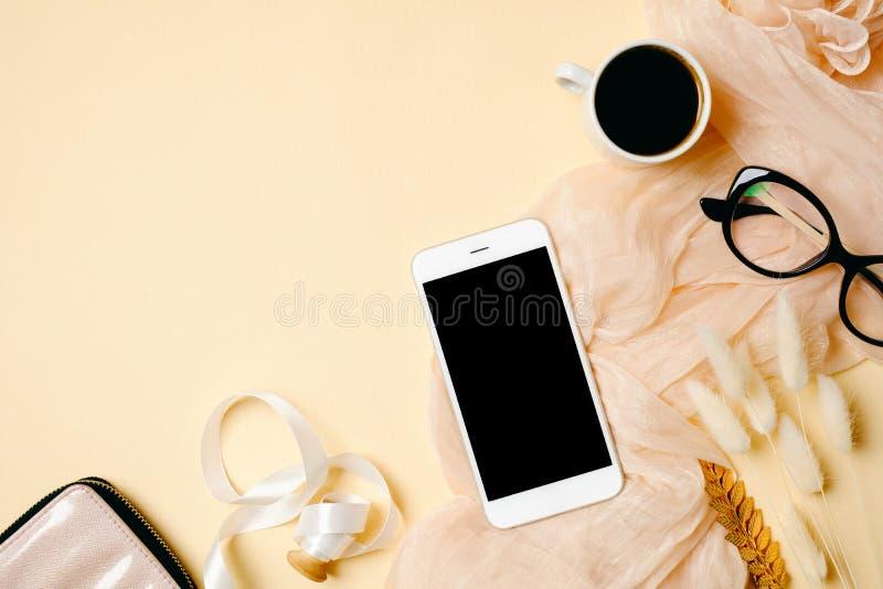 Escritorio de Ministerio del Interior de la mujer con el teléfono móvil, la taza de café, la bufanda del vidrio, de seda y los ac fotos de archivo