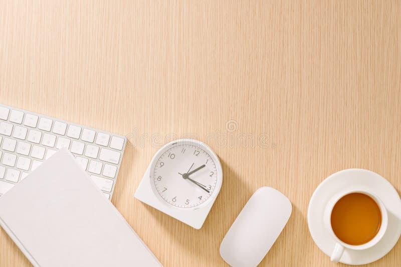 Escritorio de oficina blanco moderno con el teclado, el rat?n, el cuaderno, el reloj y la taza de caf? Visi?n superior con goma d foto de archivo