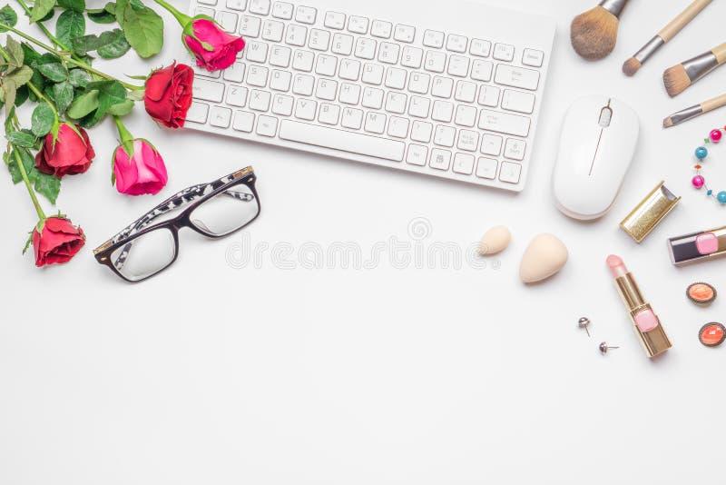 Escritorio de oficina con el teclado inalámbrico y mous, el rosa y el ramo de las rosas rojas, los cosméticos de las mujeres en e imagen de archivo libre de regalías