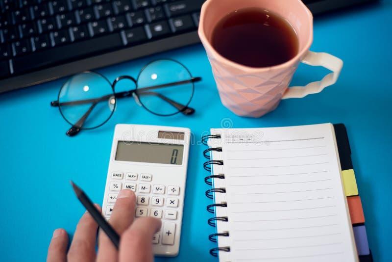 Escritorio de oficina con otras fuentes y mano masculina usando la calculadora imagen de archivo libre de regalías