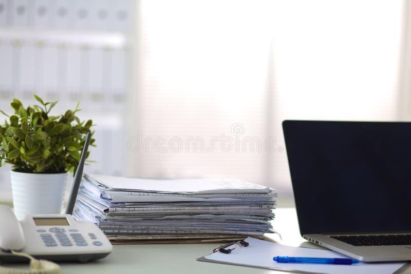 Escritorio de oficina con un ordenador y una pila de papeles imagen de archivo