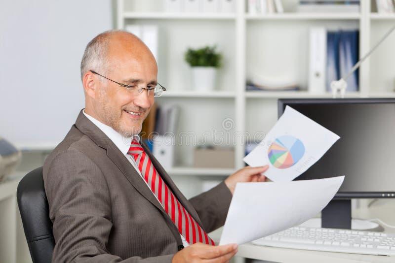 Escritorio de oficina de Analyzing Documents At del hombre de negocios fotos de archivo libres de regalías