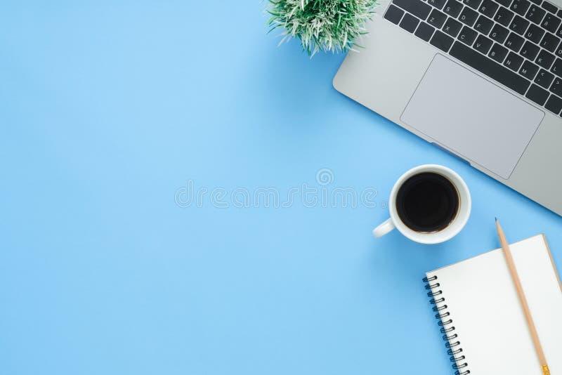 Escritorio de oficina de la visión superior con el ordenador portátil, los cuadernos y la taza de café en fondo azul del color fotos de archivo