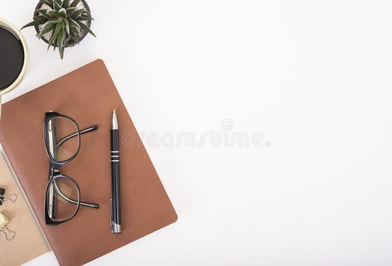 Escritorio de oficina moderno con el cuaderno, la pluma, el libro de papel y la taza de café imagen de archivo
