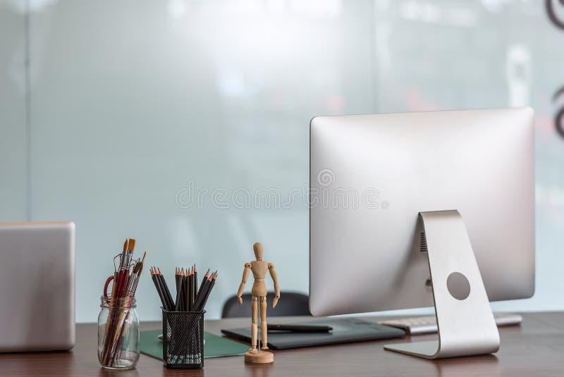 Escritorio de oficina moderno con el monitor de computadora foto de archivo