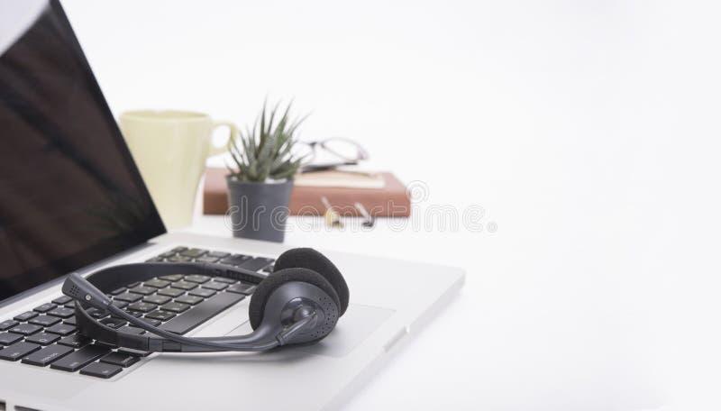 Escritorio de oficina moderno con el ordenador, cuaderno, auriculares, libro de papel fotos de archivo