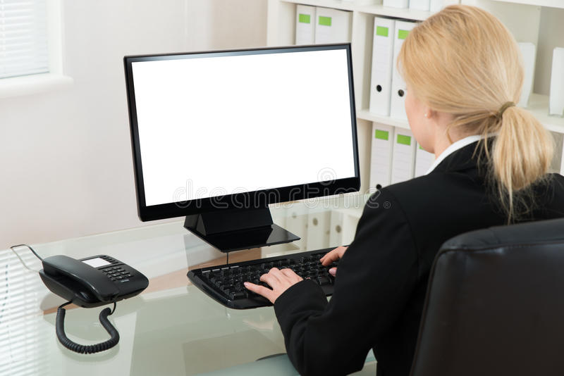 Escritorio de Using Computer At de la empresaria imagenes de archivo