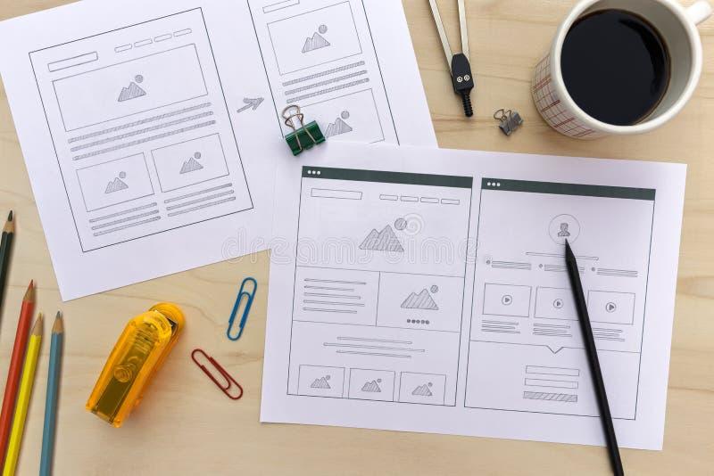 Escritorio del diseñador con bosquejos del wireframe del sitio web fotos de archivo
