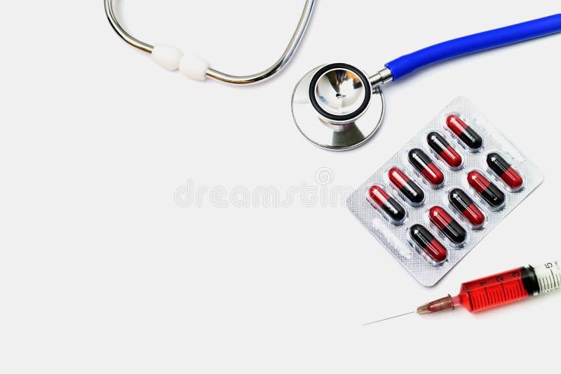 Escritorio del doctor con el equipamiento médico en el fondo blanco foto de archivo
