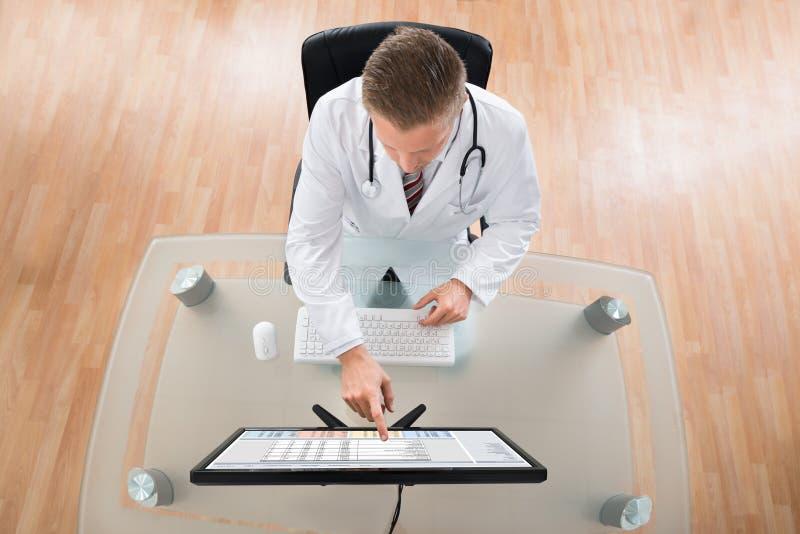 Escritorio del doctor Using Computer At imagenes de archivo
