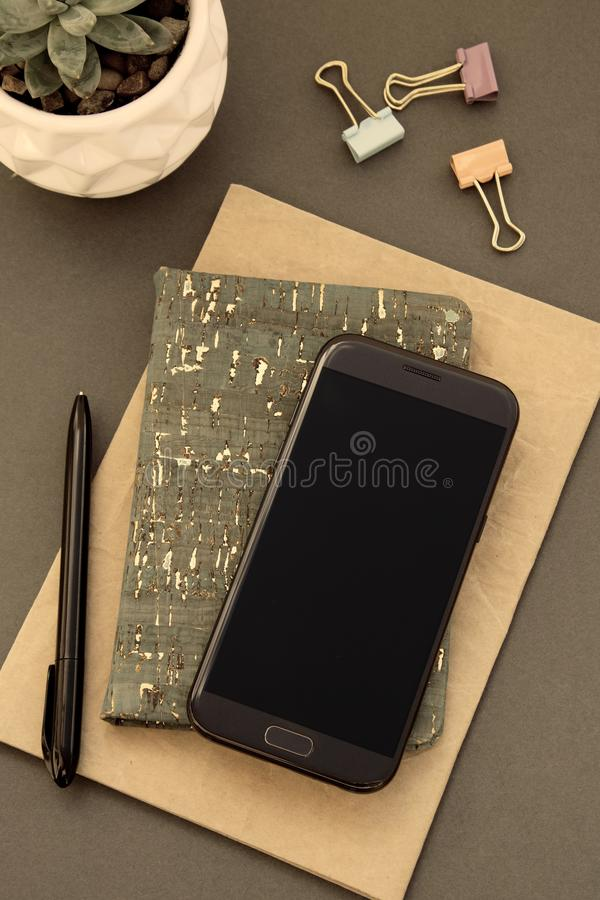 Escritorio del espacio de trabajo Endecha plana, estilo minimalistic moderno, con el cuaderno, smartphone, planta suculenta foto de archivo