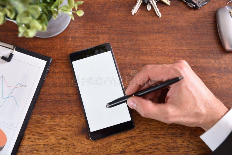 Escritorio del negocio con la mano que obra recíprocamente en el teléfono móvil con la aguja foto de archivo libre de regalías
