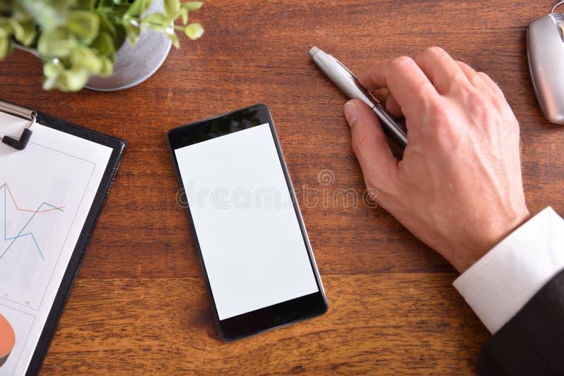 Escritorio del negocio con la mano que obra recíprocamente en el teléfono móvil con la aguja imagen de archivo libre de regalías