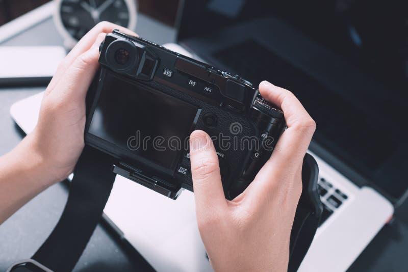 Escritorio del trabajo del fotógrafo de la cámara digital a mano fotos de archivo libres de regalías
