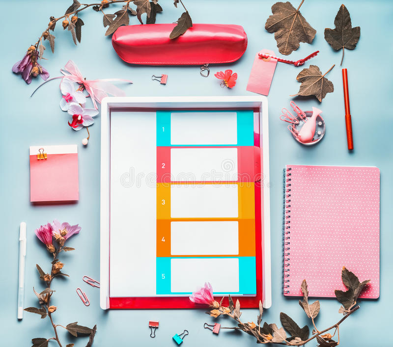 Escritorio elegante creativo de la tabla de la oficina con la fuente, diario, flores en fondo azul Endecha plana fotos de archivo libres de regalías
