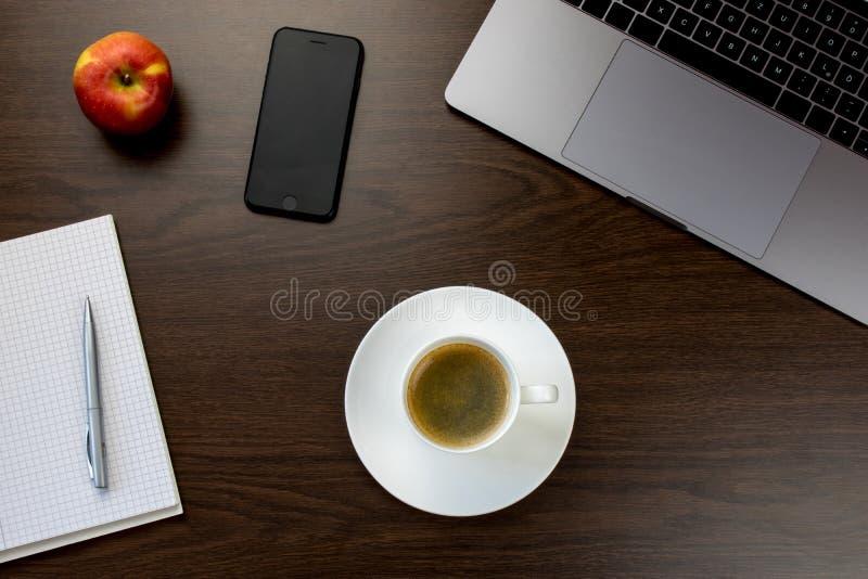 Escritorio en la oficina con un cuaderno al lado de una manzana y de un smartp foto de archivo libre de regalías