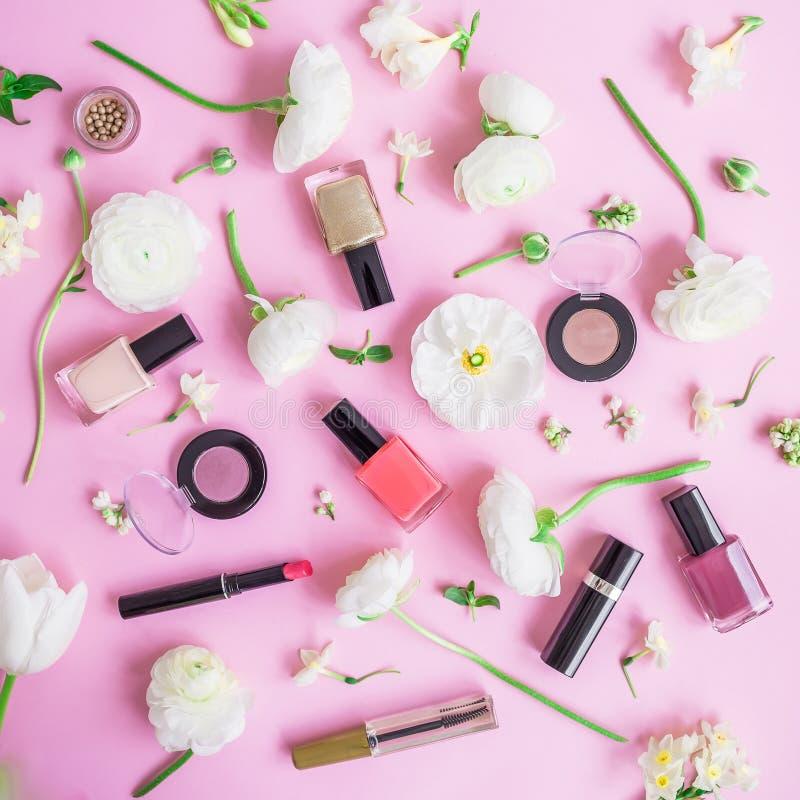Escritorio femenino con los cosméticos de la mujer y las flores blancas en fondo rosado Endecha plana, visión superior Concepto d imagen de archivo