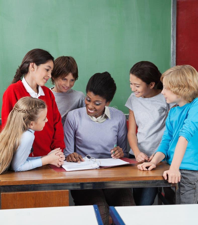 Escritorio femenino de profesor Teaching Students At foto de archivo