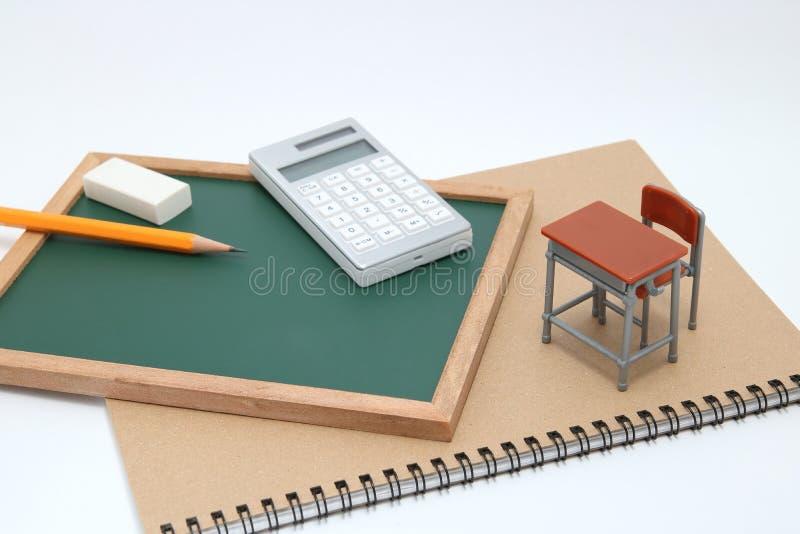 Escritorio, pizarra y calculadora miniatura de la escuela en el fondo blanco imagen de archivo