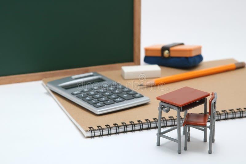 Escritorio, pizarra y calculadora miniatura de la escuela en el fondo blanco fotos de archivo libres de regalías