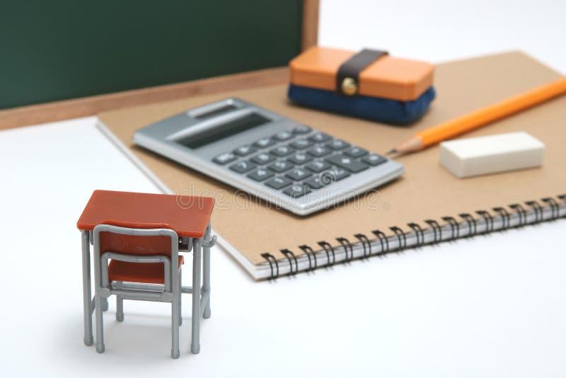 Escritorio, pizarra y calculadora miniatura de la escuela en el fondo blanco imágenes de archivo libres de regalías